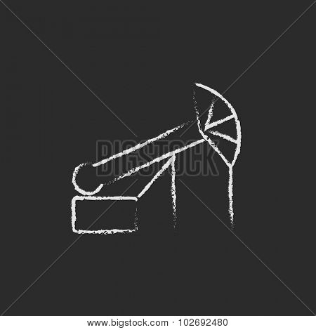 Pump jack oil crane hand drawn in chalk on a blackboard vector white icon isolated on a black background.