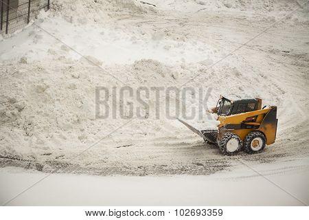 Yellow Snow Removing Bulldozer Near Big Snow Piles