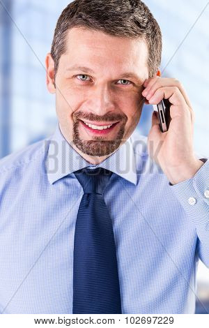 Smiling businessman making a phone call.
