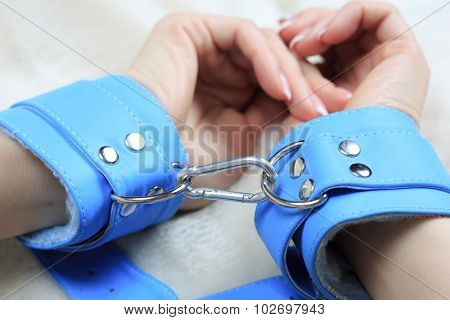 female hands in blue leather handcuffs. eagerly grabbed the sheets.. sex toys.