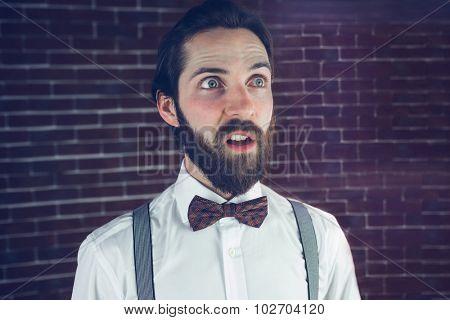 Confused man looking away against brick wall