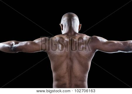 Rear view of muscular athlete with arms outstretched standing against black background