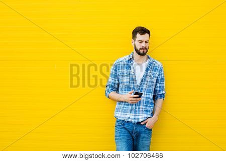 Young Handsome Man With Headphones On Yellow Wall