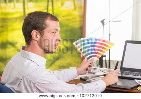 Man working on laptop while holding up palette, colormap from profile angle