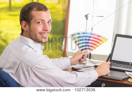 Man smiling to camera and working on laptop while holding up palette, colormap from profile angle