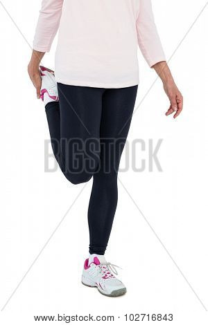 Low section of mature woman exercising over white backgrounnd