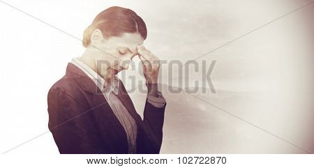 Concentrating businesswoman against trees and mountain range against cloudy sky