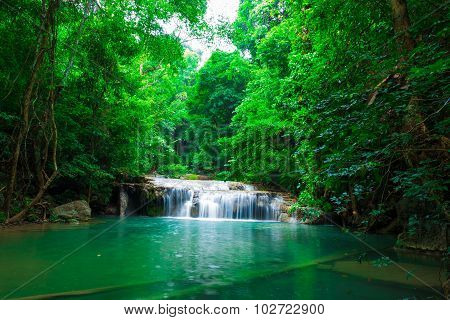 Jangle Landscape With Flowing Turquoise Water And Fish Of Erawan Cascade Waterfall