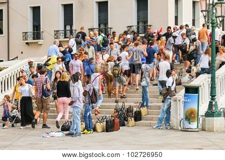 VENICE, ITALY - SEPTEMBER 2014 : Tourists walking pass vendors that sell fake hi-end fashion brand name bags and purses in Venice, Italy on September 15, 2014.