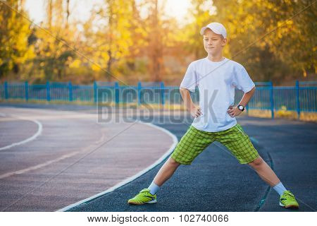 Boy Teen doing sports exercises on a stadium