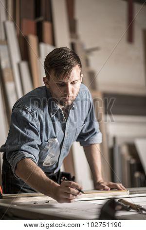 Carpenter At Work In Workshop