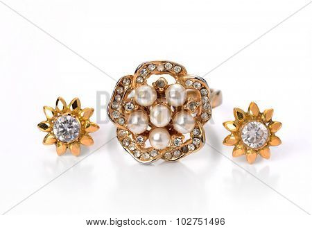 Set of golden ring and earrings with embedded pearls and diamonds.