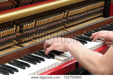 two hands playing an upright piano details