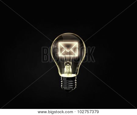 Light bulb with mail sign inside on dark background