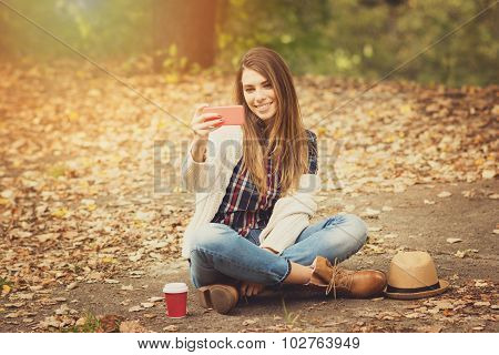 Beautiful young woman taking a selfie on smartphone in autumn