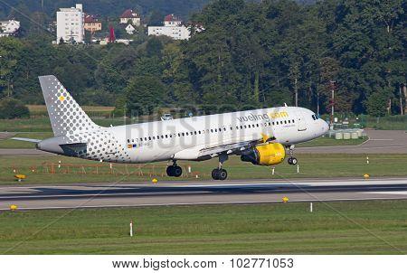 ZURICH - JULY 18: Airbus A-320 Vueling landing in Zurich after short haul flight on July 18, 2015 in Zurich, Switzerland. Zurich airport is home for Swiss Air and one of biggest european hubs.