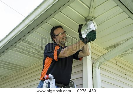 Electrician Changing A Bulb In A Outside Light Fixture
