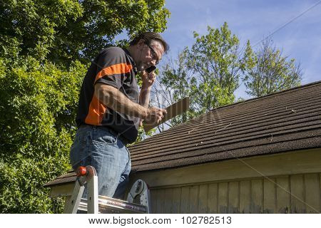 Contractor On Ladder Figuring Hail Damage Reairs To Roof