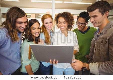 Happy businesswoman showing laptop to business people in meting room at creative office