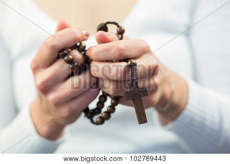 Woman holding rosary beads against white background