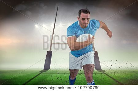 Rugby player running with the ball against rugby pitch