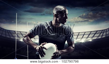 Determined rugby player holding ball against rugby stadium poster
