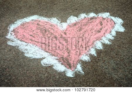 Child's sidewalk chalk drawing of pink and white heart