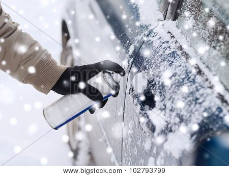 transportation, winter, people and vehicle concept - closeup of man hand with lock door de-icer