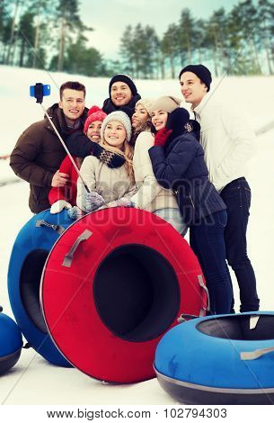 winter, leisure, sport, friendship and people concept - group of smiling friends with snow tubes taking picture by smartphone selfie stick outdoors