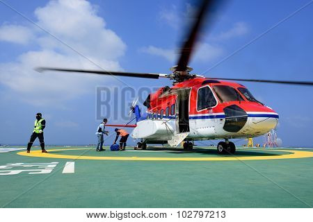 The officer take care passenger and load baggage to helicopter at oil rig platform