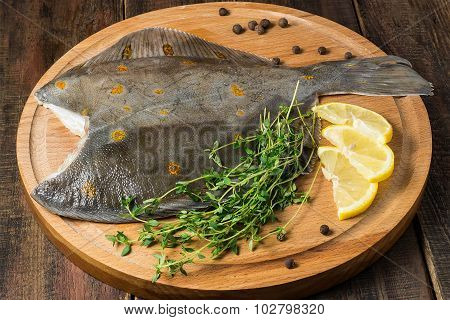 Fresh Raw Plaice With Pepper, Thyme And Lemon On The Board