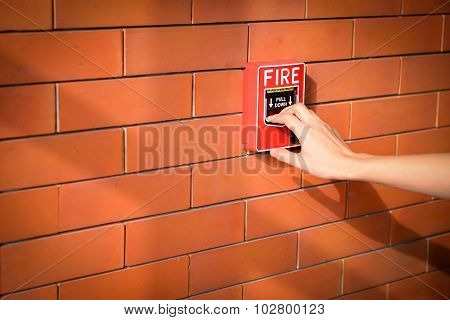 The hand of woman is pulling fire alarm on the brick wall
