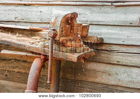 Old rusty clumping device on weathered work bench