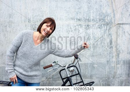 Portrait of a cheerful older woman with bike poster