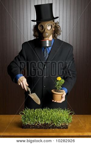 Businessman wearing a gasmask holding a potting shovel and a flower standing over a patch of grass poster