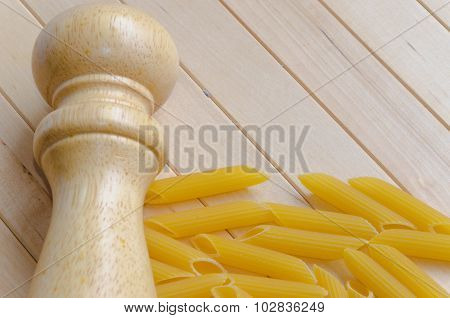 Pasta with salt caster on wooden background