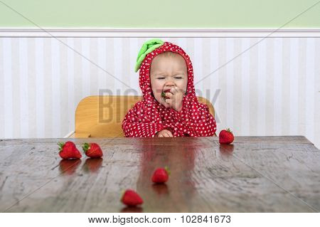 Happy Baby In Berry Suit Eating Strawberries