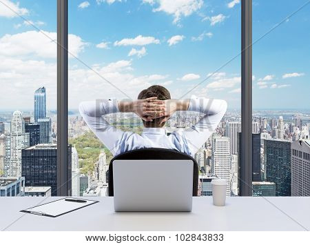 Rear View Of The Relaxing Businessman With Crossed Hands Behind His Head, Who Is Looking At The Cntr