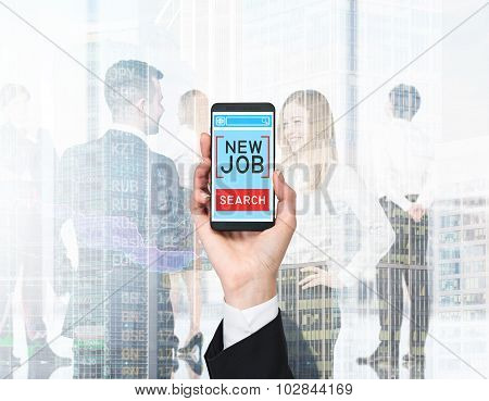A Hand Holds A Smartphone With The Text 'new Job Search' On The Screen. A Business Couple In Blur Is