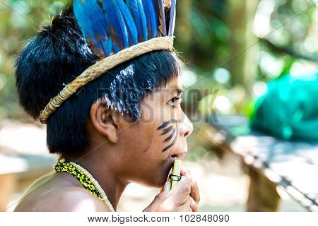 Native Brazilian boy playing wooden flute at an indigenous tribe in the Amazon