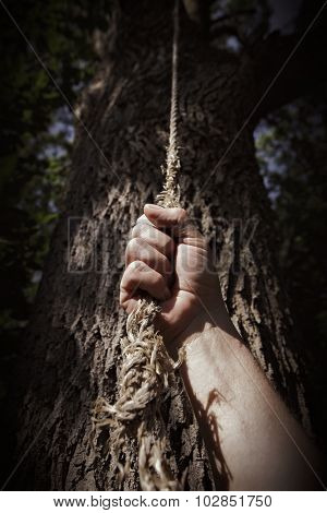 Man's hand grasping an old worn rope