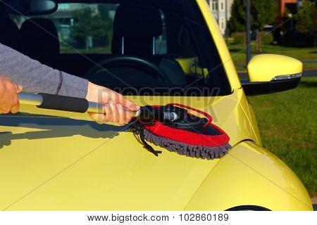Hand with brush washing a car. Waxing and polishing.