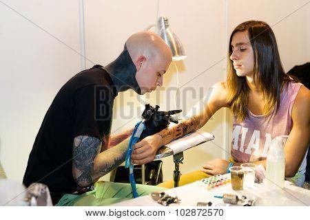 Minsk, Belarus - September 19, 2015: Professional Artist Doing Tattoo On Client Hand.