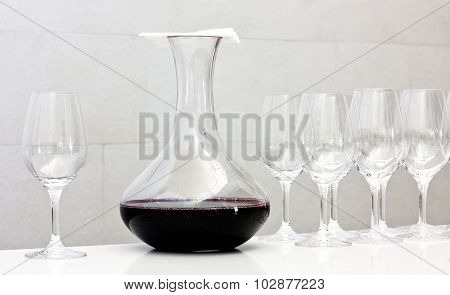 Wine tasting: a decanter of red wine covered by a napkin and a row of glasses
