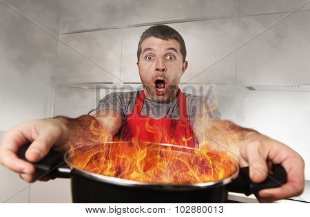 Inexperienced Home Cook With Apron Holding Pot Burning In Flames With Stress Panic Face Expression
