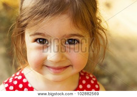 Cute little girl smiling in sunny summer day outdoors