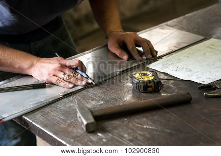 Metalworker Marking Measurements On Metal