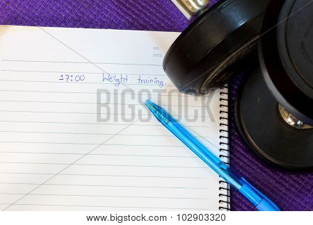 Word In Notebook,pen ,dumbbell  On Mat Background.