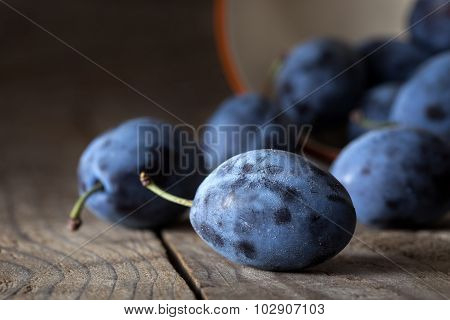 Plums on a dark wooden table background