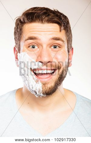 Happy young man with shaving cream foam on half of face beard. Handsome guy preparing to shave. Skin care and hygiene. poster
